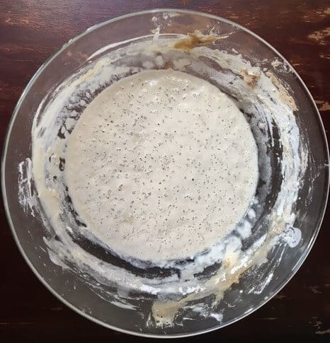 A glass bowl of bubbling, ripe sourdough starter.