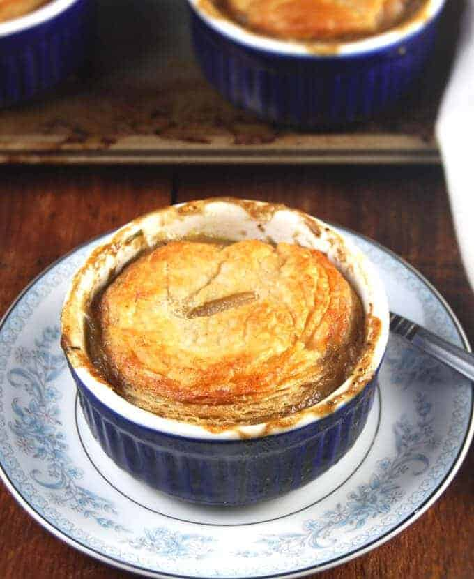 A bubbling, savory vegan pot pie with mushrooms, carrots, celery, green peas and onions in an individual blue ramekin on a blue and white plate with more pot pies in the background