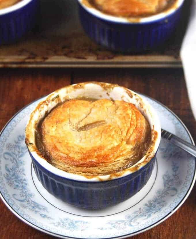 Photo of a bubbling, savory vegan pot pie with mushrooms, carrots, celery, green peas and onions in an individual blue ramekin on a blue and white plate with more pot pies in the background