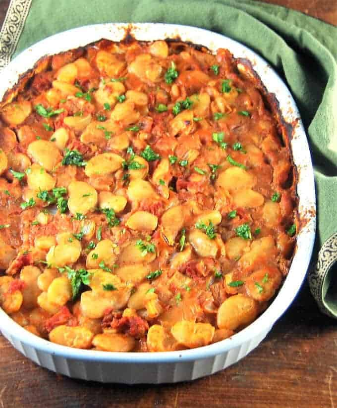 A white oval baking dish with Greek gigantes plaki beans simmered and baked in a tomato, oregano and thyme sauce.