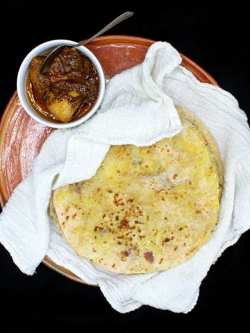Aloo Parathas stacked on an earthenware dish and nestled inside a white flour sack cloth with a white ceramic bowl of Indian lime pickle on the side with a silver spoon, all on a black background