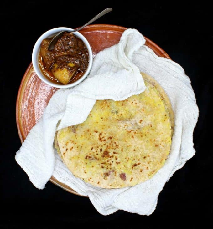 An overhead shot of a stack of freshly baked aloo parathas nestled in a white flour sack towel on an earthenware plate with a small ceramic bowl of Indian lime pickle on the side, all on a black background.