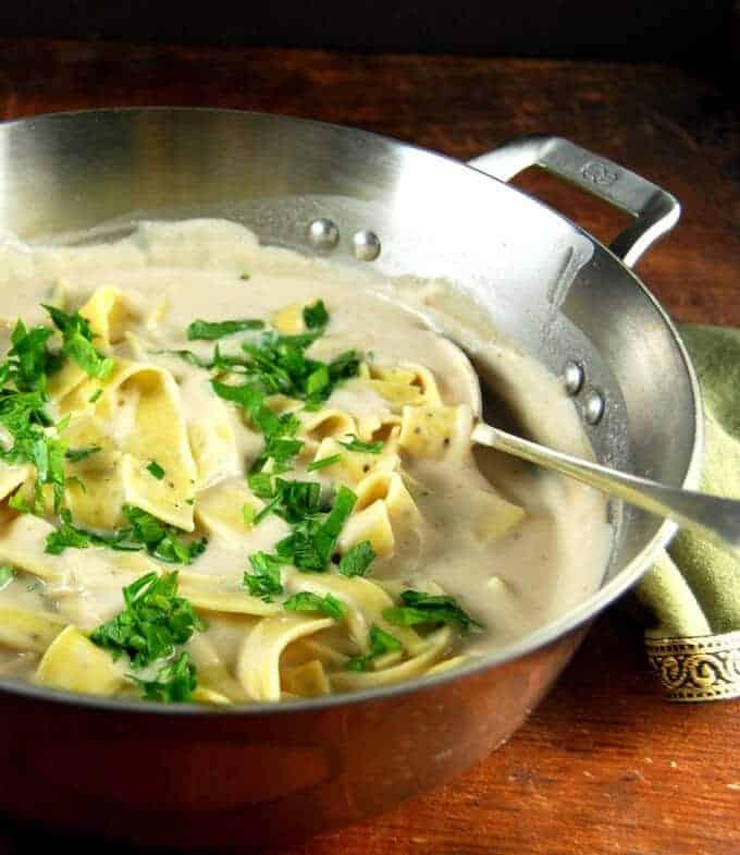 Best Vegan White Pasta Sauce in steel saucepan with pasta and parsley.