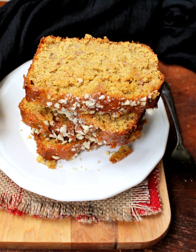 A stack of slices of vegan Orange almond breakfast loaf on a white plate.