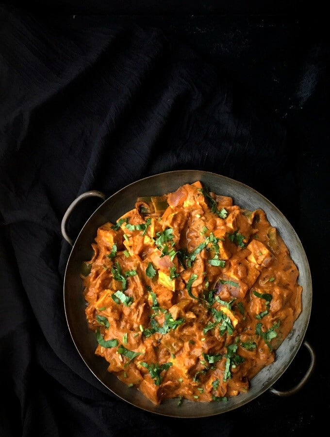 Tofu Tikka Masala in a serving copper pan with tofu cubes in tomato onion sauce with spices like turmeric and cayenne and garnished with cilantro.