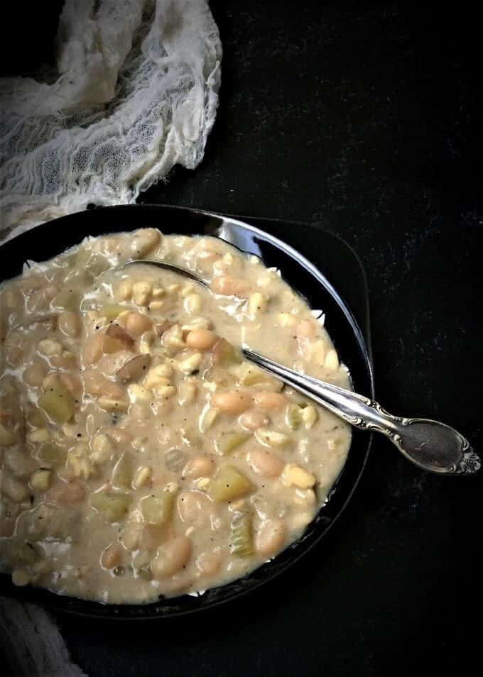 Vegan Chesapeake Chowder in a black bowl with silver spoon.