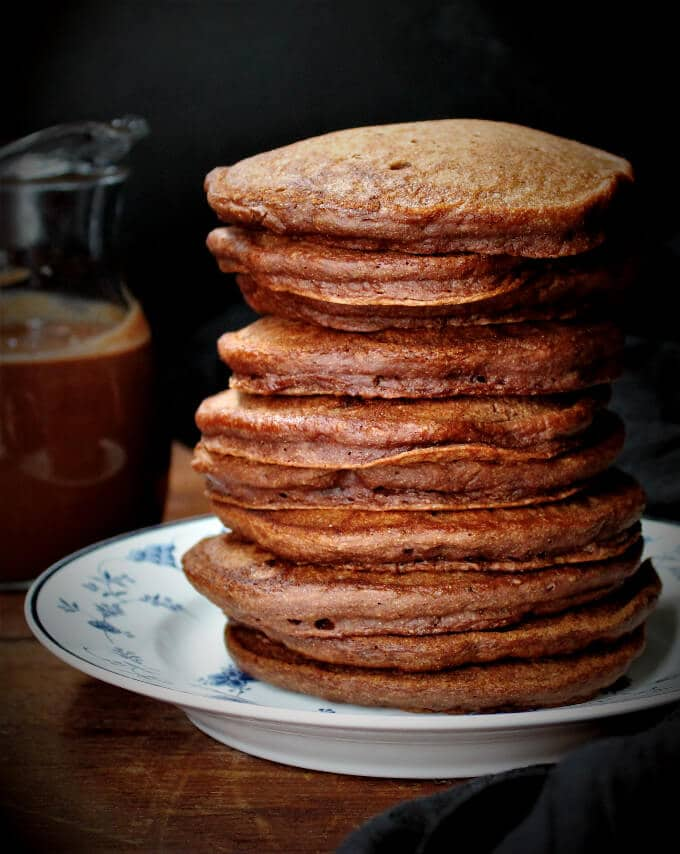 A tall stack of vegan chocolate pancakes on a plate with chocolate sauce in background.