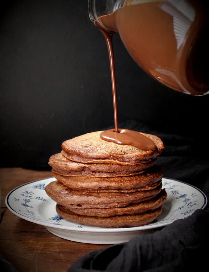 Photo of silky chocolate sauce being poured over chocolate pancakes.
