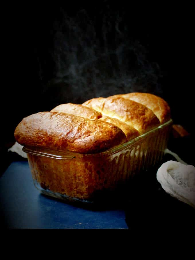 A loaf of a sectioned vegan brioche with olive oil in a glass loaf pan against a black background with a white cheesecloth next to it