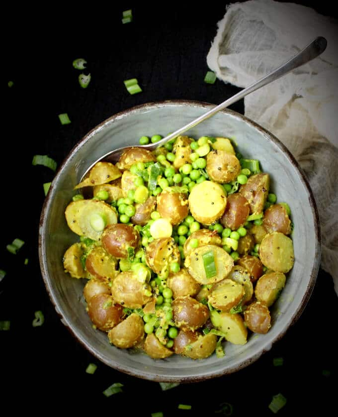 Vegan Indian-style Potato Salad with Turmeric and Green Peas in a bowl