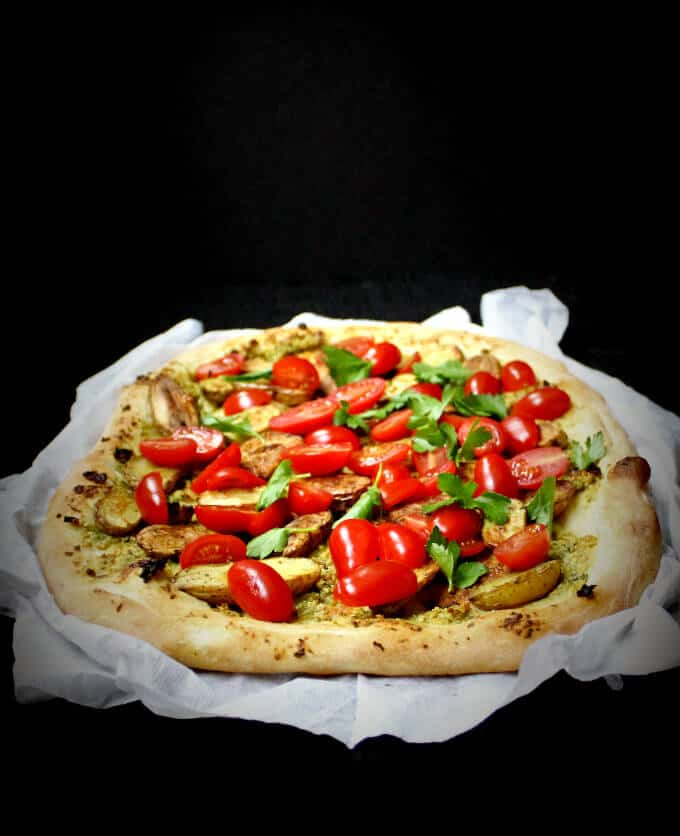 Side shot of golden pizza crust with fingerlings and cherry tomatoes