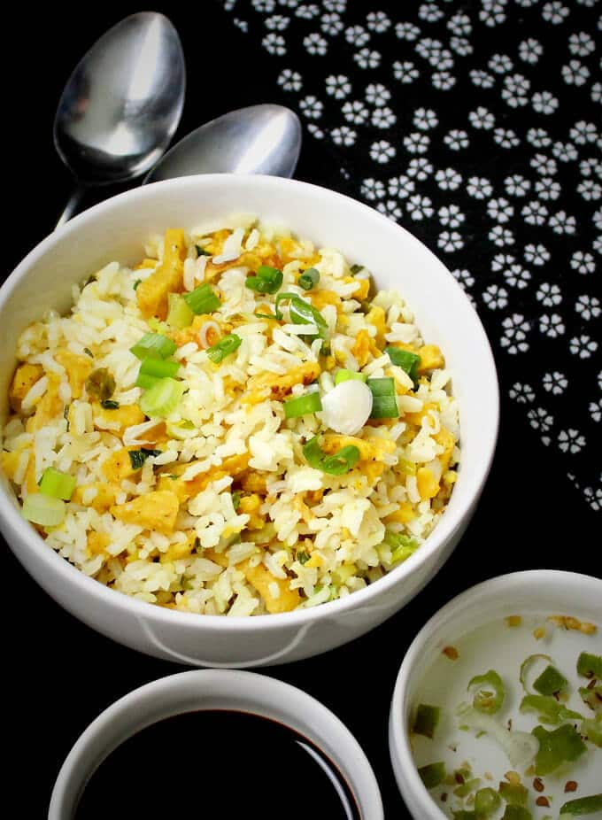 White bowl with vegan Indo Chinese Egg Fried Rice with chilli vinegar sauce and soy sauce on the side | HolyCowVegan.net