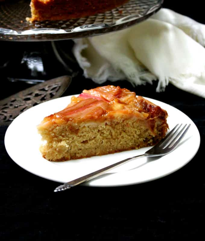 A slice of soft, fluffy, vegan rhubarb ginger upside down cake with a mosaic-like top of pink rhubarb on a white plate with a fork.