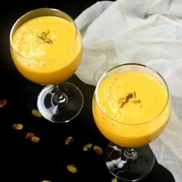 Two glasses of vegan mango lassi with pistachio garnish