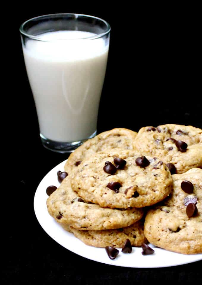 Front shot of Vegan Chocolate Chip Cookies in a white plate with a glass of almond milk - HolyCowVegan.net