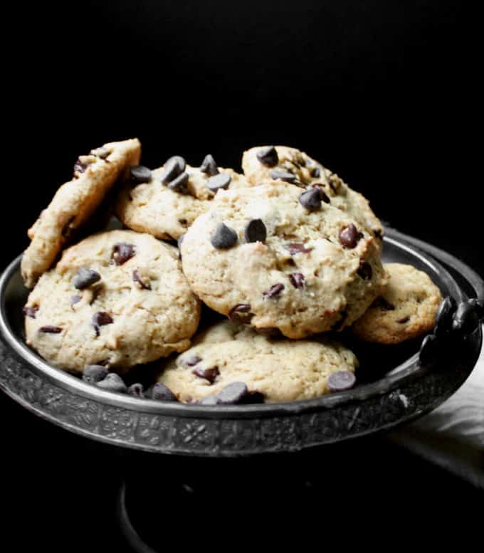 A heap of vegan chocolate chip cookies on a silver server