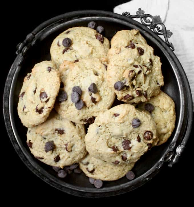 A steel serving tray with vegan chocolate chip cookies on a black background with a white kitchen towel.