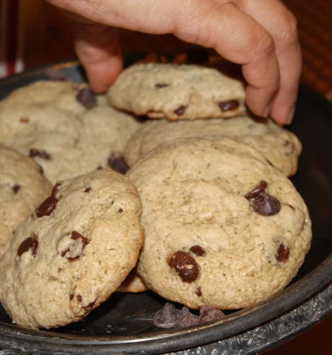 A hand picking up a vegan chocolate chip cookie from a silver serving plate