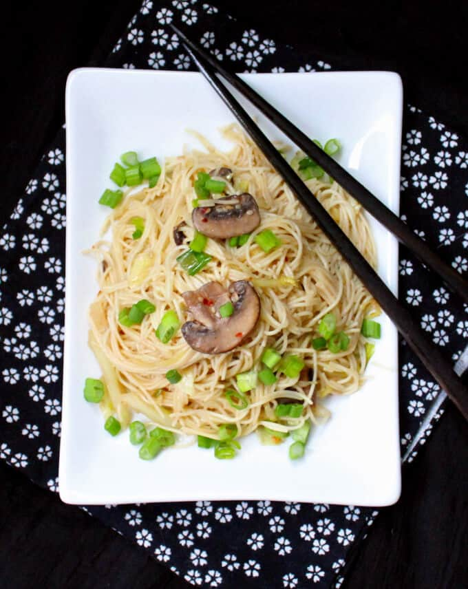 View from above of a rectangular plate of Vegan Chinese Longevity Noodles with Mushrooms and Ginger with chopsticks - HolyCowVegan.net
