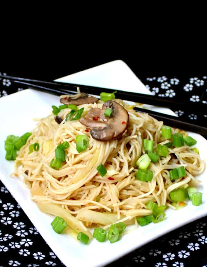 A white plate with Vegan Chinese Longevity Noodles with Mushrooms and Ginger on a black and white flowered napkin - HolyCowVegan.net