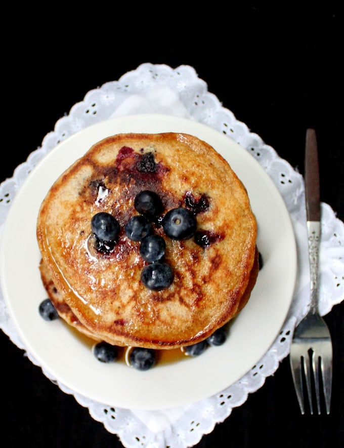 Top shot of Vegan Sourdough Blueberry Pancakes with blueberries topping the pancakes on a white lace napkin background - HolyCowVegan.net