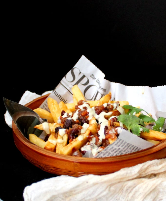 Front shot of Vegan Chili Fries in a bamboo basket cradled in newspaper and drizzled with a creamy, cheezy horseradish sauce - HolyCowVegan.net