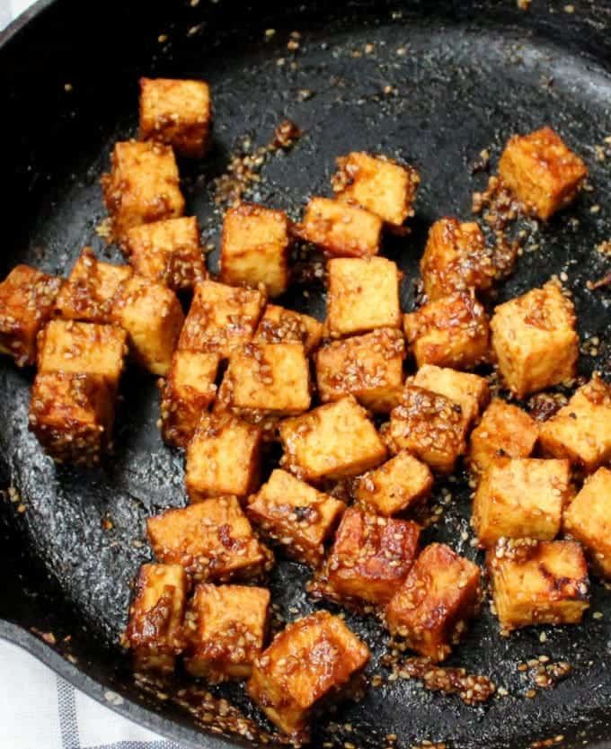 Cubes of tofu with sesame seeds and seasonings frying in a black cast-iron skillet