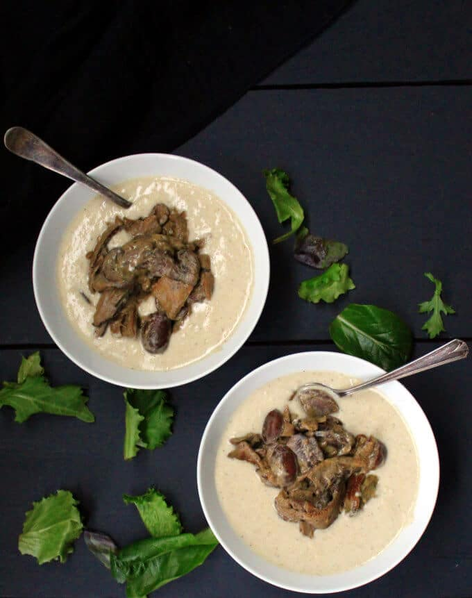 An overhead shot of two bowls of creamy polenta and wild mushrooms with greens scattered around on a black background