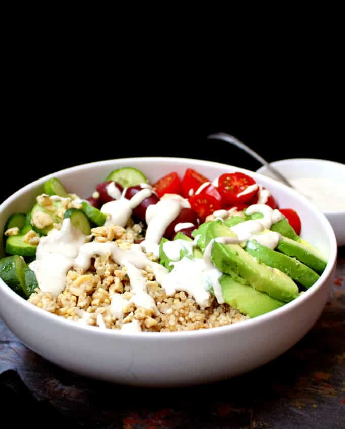 Front partial view of a white bowl with Greek Goddess salad bowl with avocados, tomatoes, cucumbers, tempeh and quinoa against a black background