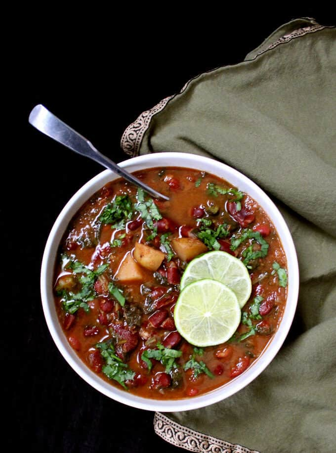Top shot of Instant Pot Kidney Beans Curry, Rajma, in a white bowl against a black background - HolyCowVegan.net