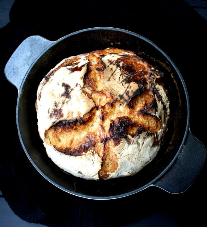 Sourdough bread baked in a dutch oven against a black cheesecloth background