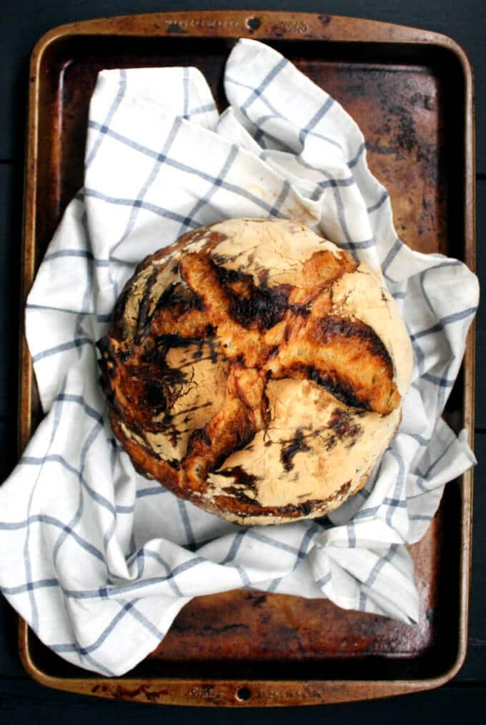 Top shot of a sourdough boule with a split top on a kitchen towel atop a baking sheet