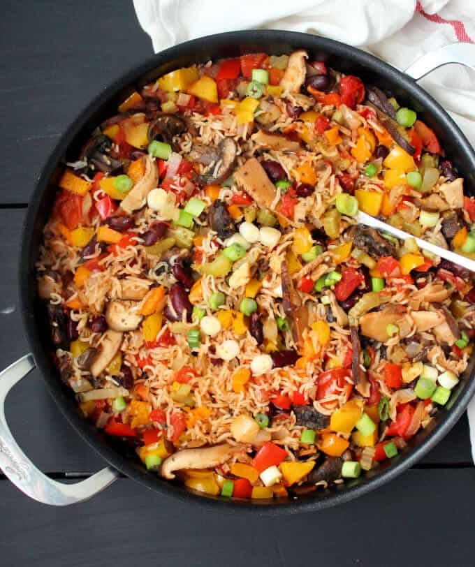 A black saucepan on a grey background with rice, mushrooms, peppers, black beans and a serving spoon.
