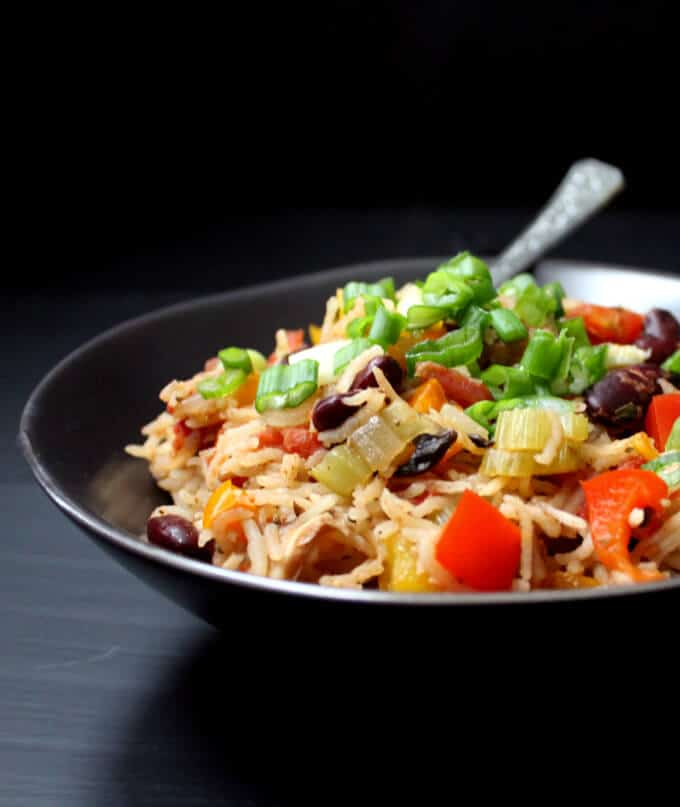 A black bowl with vegan jambalaya, rice, red, yellow and orange peppers, scallions, black beans, rice and other vegetables against a black background
