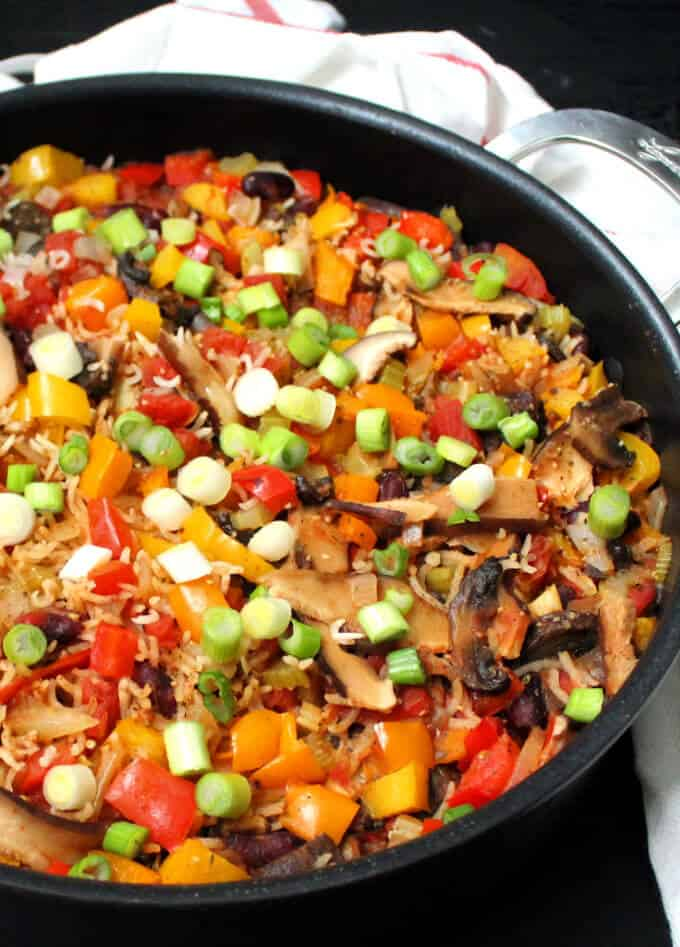 Photo of vegan jambalaya in a black skillet with celery, mushrooms, onions, bell peppers and scallions.