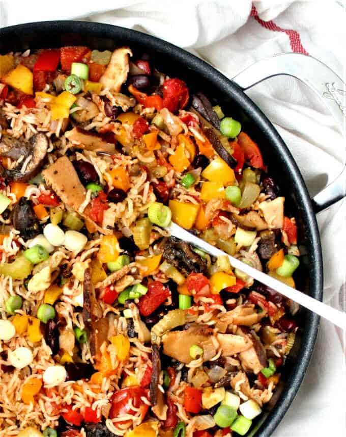 Photo of a colorful vegan jambalaya with bell peppers, mushrooms, celery and onions in a black saucepan with a serving spoon.