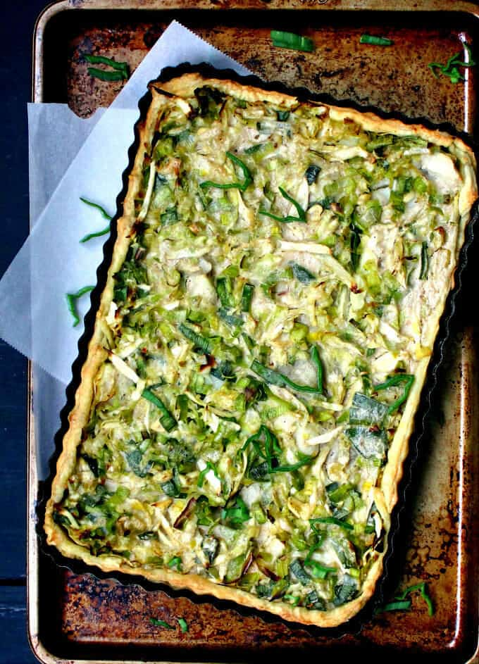 A cabbage leek and potato tart in a tart pan sitting on a baking sheet