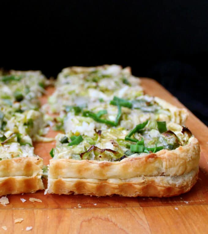 Slices of Cabbage Leek Potato Tart on a wooden chopping board against a black background