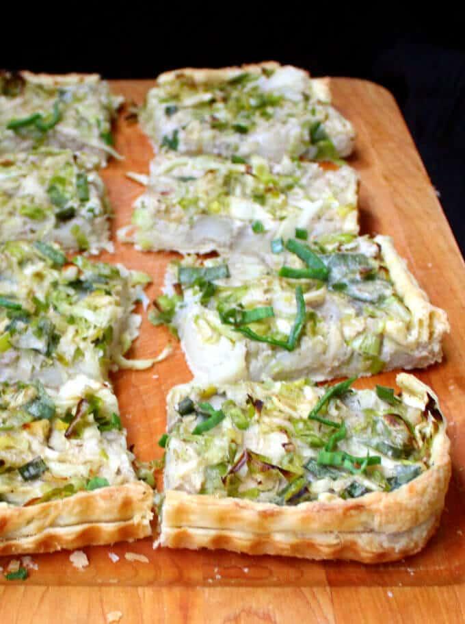 Slices of  vegan Irish cabbage, leek and potato tart on a  chopping board.