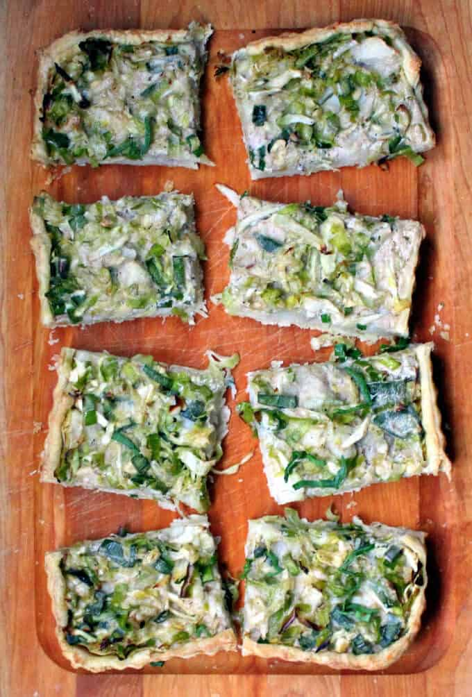 Slices of cabbage and potato colcannon tart on a wooden chopping board