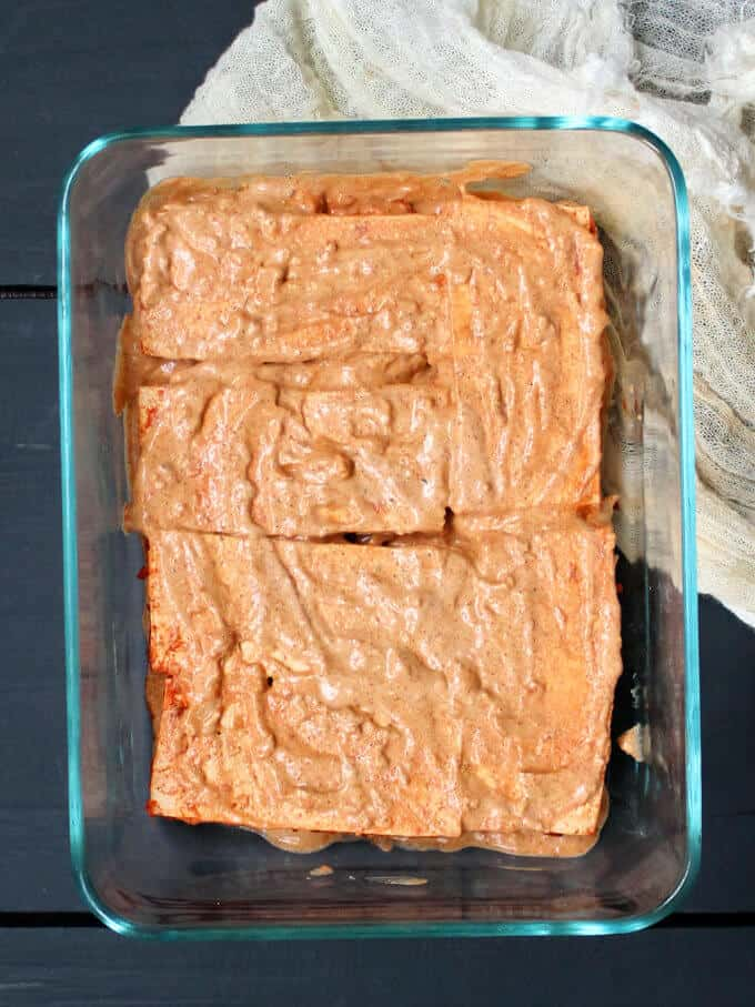 Slices of tofu in a baking dish rubbed with a marinade of cashew yogurt, ginger, garlic, paprika or Kashmiri chili powder and salt