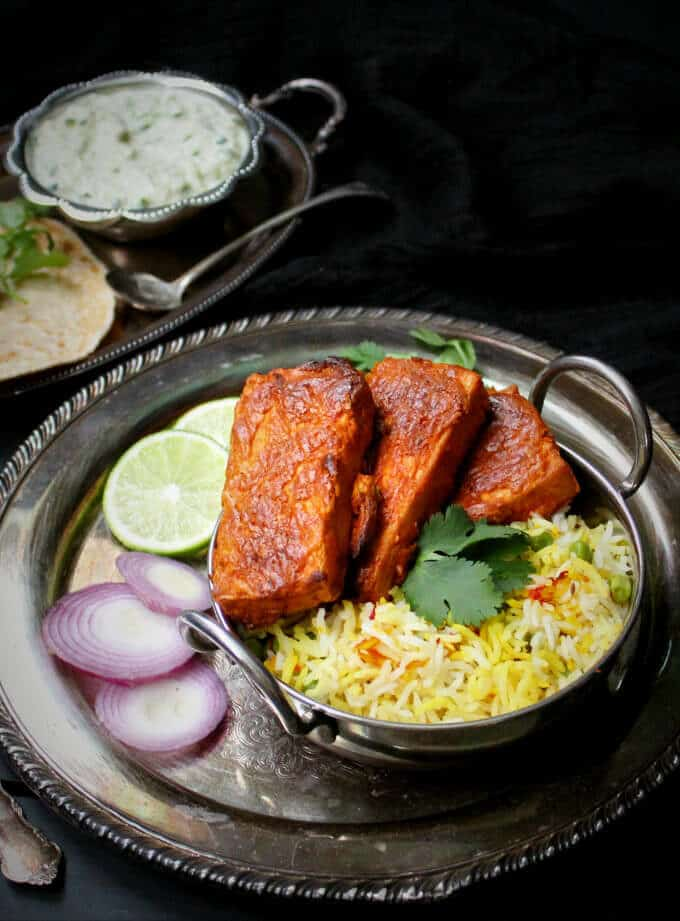 Oven Blackened Tandoori Tofu in a small Indian wok with pilaf rice and raita and roti on the side on a silver tray against a black background - HolyCowVegan.net