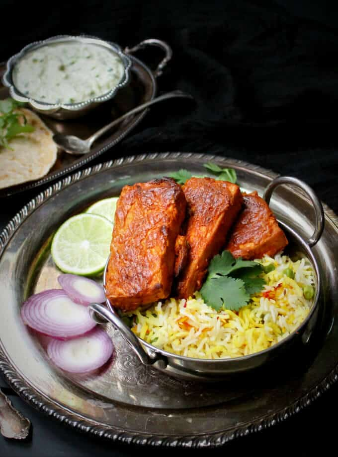 Oven Blackened Tandoori Tofu in a small Indian wok with pilaf rice and raita and roti on the side on a silver tray against a black background