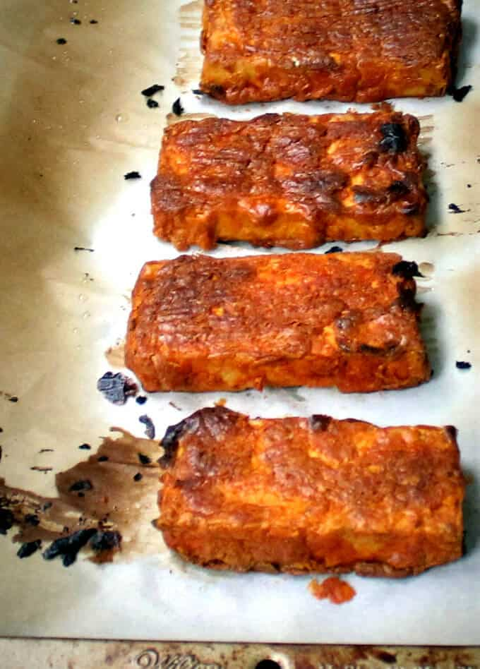 Slices of baked tandoori tofu on parchment paper on a baking sheet
