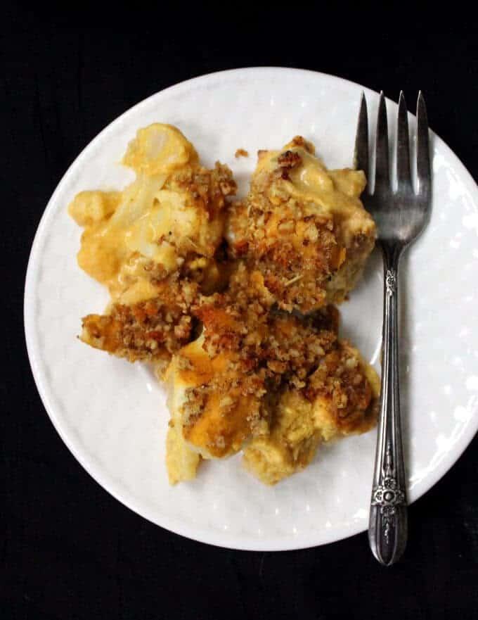 Overhead shot of Vegan Cauliflower Cheese in a white plate against black background and a fork. #vegan #glutenfree #soyfree #gratin #cassrerole. HolyCowVegan.net