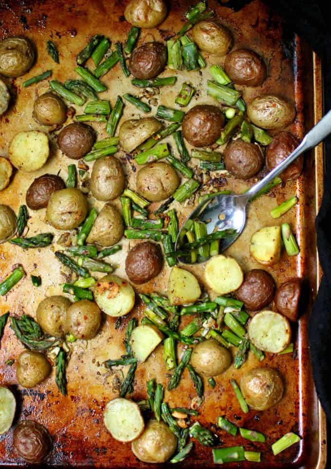 Garlicky Roasted Asparagus and Potatoes on a baking sheet witha  spoon.