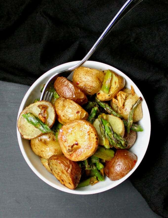 Overhead photo of a white bowl with golden roasted asparagus and potatoes with a fork.