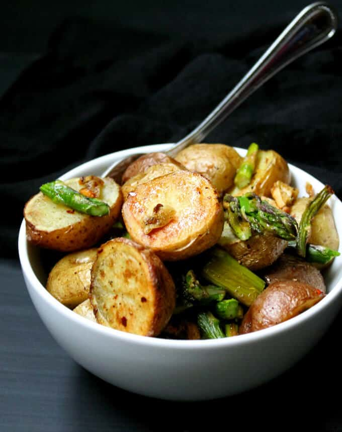 Photo of a white ceramic bowl with garlicky roasted asparagus and potatoes with a fork.