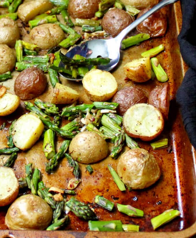Photo of Garlicky Roasted Asparagus and Potatoes on a baking sheet with a serving spoon.