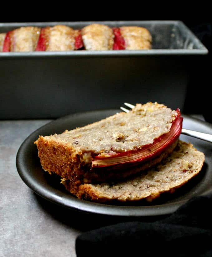 Photo of a vegan rhubarb bread baked in a loaf pan with two slices in a black plate.